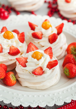 Pavlova meringue cake decorated with fresh strawberry and cape gooseberry on festive background Banco de Imagens