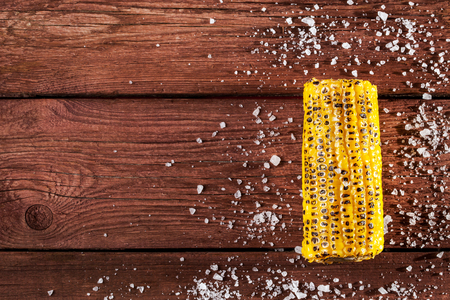 sal: Fresh grilled corn cob with salt on wooden table, copy space, top view