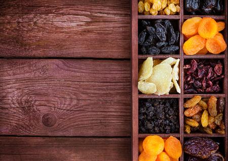 Verschiedene getrocknete Früchte in Holz Feld Drucker-Feigen, Rosinen, Datum, Preiselbeeren, Johannisbeeren, Birnen, Ingwer und Aprikosen. Draufsicht.