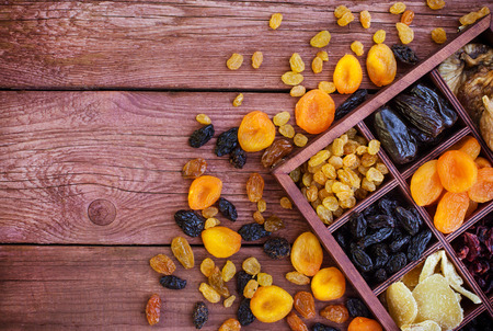 frutas secas: Assorted  dried fruits in wooden printers box-figs, raisins, date, cranberries, currant, pears, ginger and apricots. Top view.