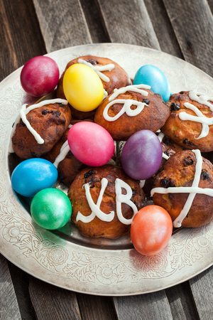 easter cross: Easter hot cross buns and colored eggs on plate