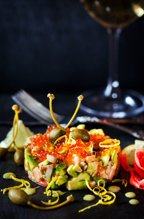 Delicious red caviar, salmon and avocado tartar, dark background Stock Photo