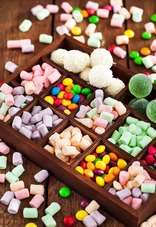 dragee: Mix of candies and sweets in wooden printers box - marshmallows, candies, dragee, fruit jelly Stock Photo
