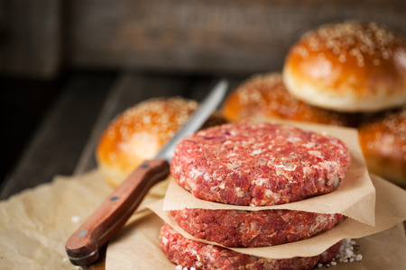 ready to cook food: Raw ground beef meat steak cutlets and burger buns on  wooden background, ready for cooking
