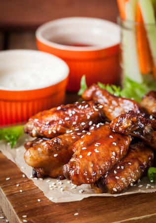 Spicy hot chicken wings cooked with honey and soy,  topped with sesame seeds, served with sauce, celery and carrot sticks Stockfoto