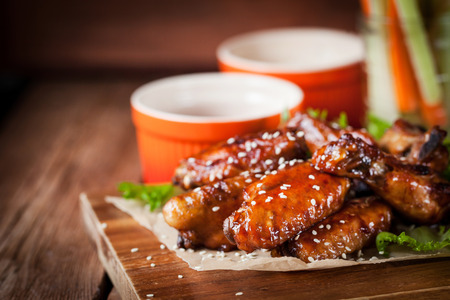 Spicy hot chicken wings cooked with honey and soy,  topped with sesame seeds, served with sauce, celery and carrot sticks Stock Photo
