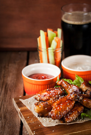 Spicy hot chicken wings cooked with honey and soy,  topped with sesame seeds, served with sauce, celery and carrot sticks and dark beer