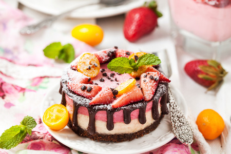 Delicious individual mini cake (cheesecake) decorated with chocolate and strawberry Stock Photo