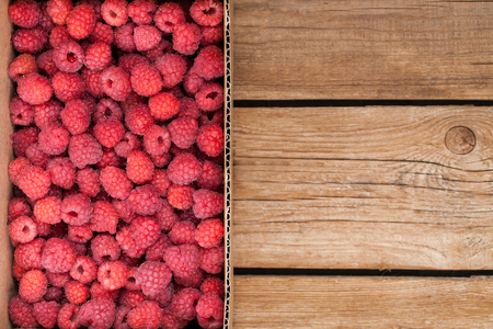 gamme de produit: Fresh organic ripe raspberry in box on wooden table with copy space