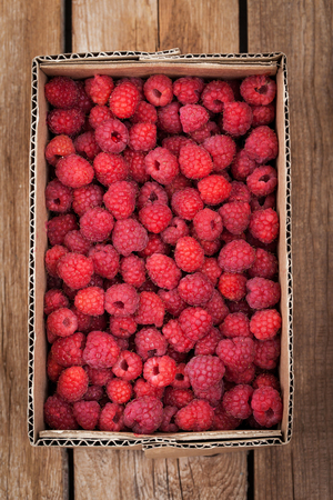 gamme de produit: Fresh organic ripe raspberry in box on wooden table Banque d'images