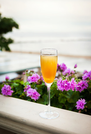 Glass of italian Bellini alcoholic cocktail with peach  on the evening beach Stock Photo