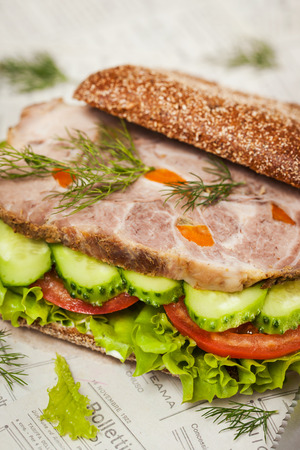roast meat: Close-up of tasty rye bread sandwiches with roast meat and vegetables, on wooden background