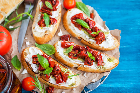 relish: Bruschetta with cream cheese, pesto, fresh basil and sun dried tomatoes on blue rustic wooden table