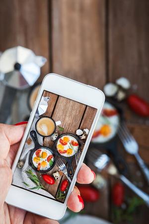 Kız, kızartılmış yumurta ile kahvaltı yiyecek fotoğraf çekerken cep telefonu akıllı telefonlarla el ele geçiriyor Stok Fotoğraf