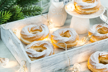 profiterole: Cream puff rings (choux pastry) on white christmas background