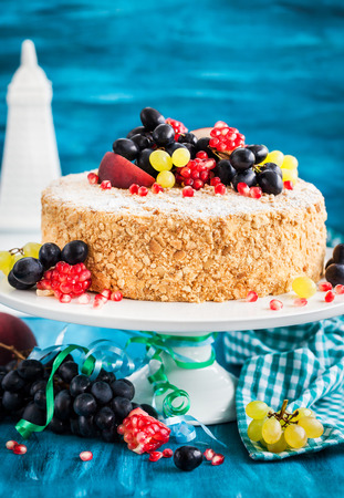 Delicious homemade honey cake decorated with fresh fruits and berries