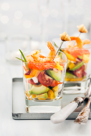 Shrimp, avocado, tomato, salmon and red caviar cocktail salad served in a glass