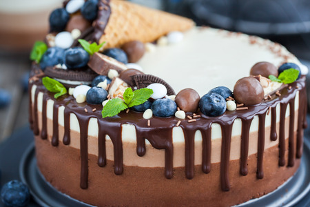 three layered: Delicious three chocolate mousse cake decorated with waffle cone, fresh blueberry, mint, candies and frosting