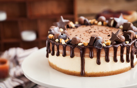 Delicious two-ply chocolate cheesecake decorated with candies and frosting Stock Photo