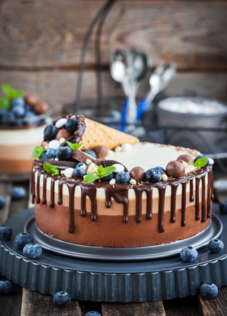 Delicious three chocolate mousse cake decorated with waffle cone, fresh blueberry, mint, candies and frosting
