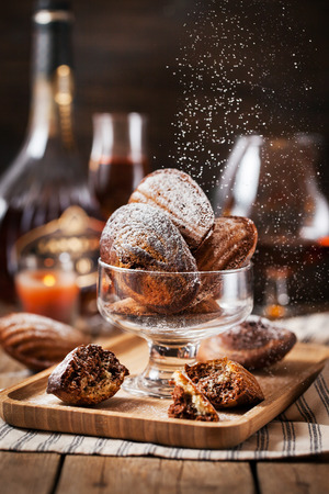 Homemade black and white marbled madeleines cookies and sugar powder motion