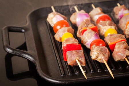 Fresh turkey meat skewers with cherry tomatoes, pepper and onion cooking on grill pan