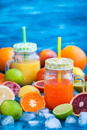 Citrus vitamin juice in mason jars with fresh oranges, mandarins, lemons and limes around, healthy drink