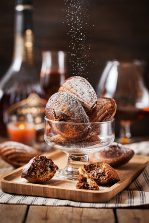 confectionery: Homemade black and white marbled madeleines cookies and sugar powder motion Stock Photo