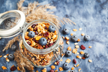Homemade granola in jar and fresh blueberry, healthy breakfast of oatmeal muesli, nuts, seeds and dried fruit
