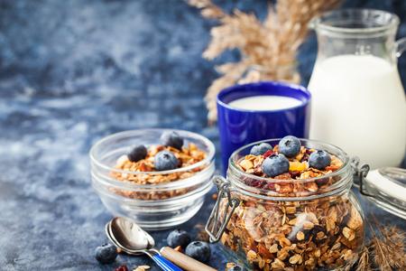 Homemade granola in jar, fresh blueberry and milk, healthy breakfast of oatmeal muesli