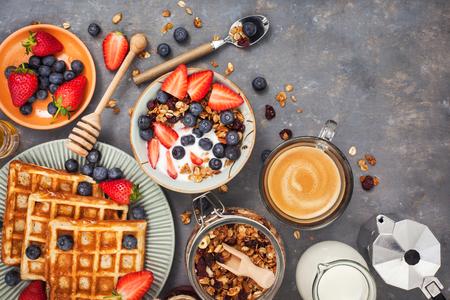 シリアル グラノーラ、牛乳、新鮮な果実、コーヒーやワッフル、トップ ビューで健康的な朝食用のテーブル