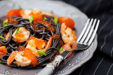 Black spaghetti with shrimps and red caviar on dark background Stock Photo