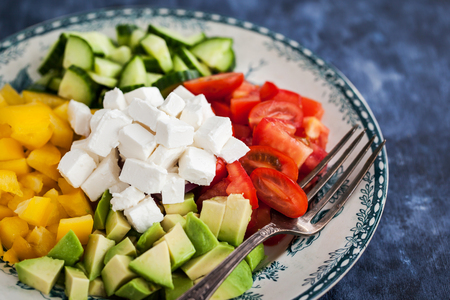 desk: Fresh delicious tomato, bell pepper, cucumber, avocado, onion and feta salad