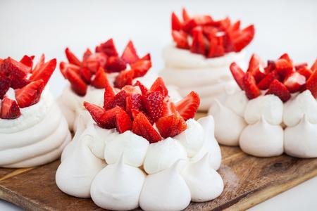 Delicious mini Pavlova meringue cake decorated with fresh strawberries