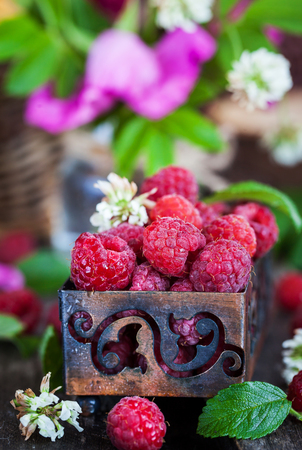 gamme de produit: Fresh organic ripe raspberry in box with summer flowers on background Banque d'images