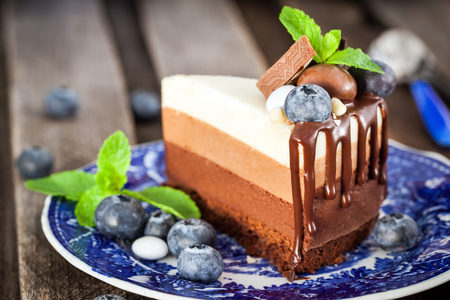 Piece of delicious three chocolate mousse cake decorated with fresh blueberry, mint and candies