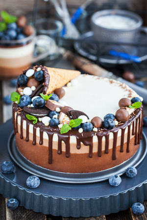 cuerno de la abundancia: Delicious three chocolate mousse cake decorated with waffle cone, fresh blueberry, mint, candies and frosting