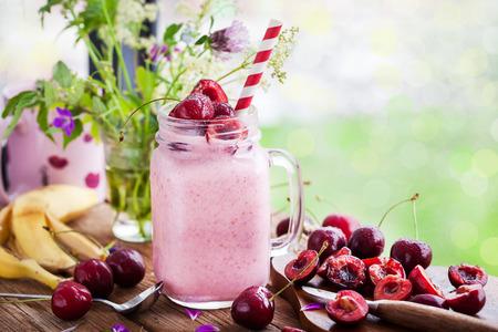 Verse zelfgemaakte gezonde bessen smoothie in metselaar pot op ramen achtergrond Stockfoto
