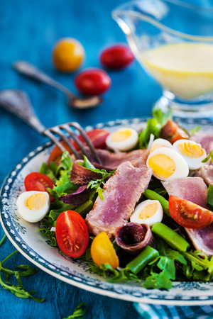 Tuna salad ( Nicoise) with tomatoes, boiled eggs, onion, anchovy and lettuce