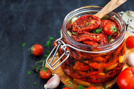 Sun dried tomatoes with garlic and olive oil in a jar on dark background Stock fotó - 87157958