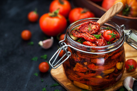 Sun dried tomatoes with garlic and olive oil in a jar on dark background