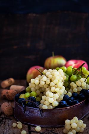 cuerno de la abundancia: Uva fresca blanca, verde y morada madura en la oscuridad