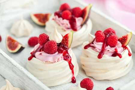 Delicious mini Pavlova meringue cake decorated with fresh raspberry, figs  and berry sauce on white background