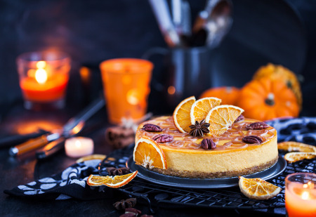 Delicious pumpkin and orange cheesecake decorated with caramel sauce and pecan Stock Photo