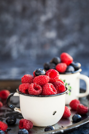 Fresh ripe blueberry and raspberry in enamel mugs