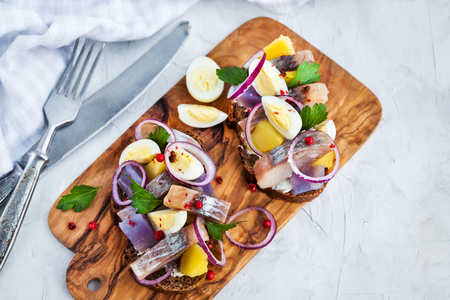 Open sandwich (smorrebrod) with herring, onion, potato and eggs
