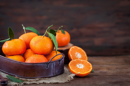 Fresh tangerines with leaves on  wooden table