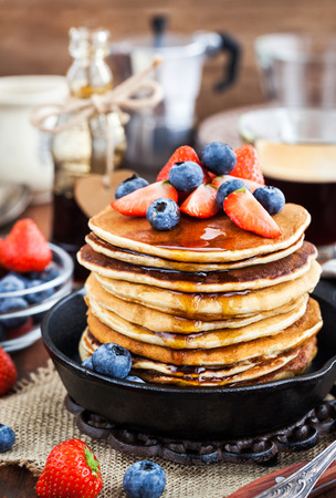 Stack of freshly prepared banana  pancakes with fresh berries and maple syrup for breakfast