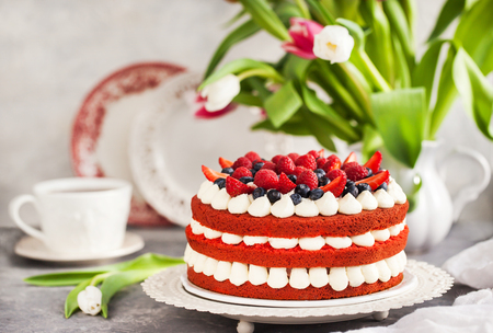 Delicious homemade red velvet cake decorated with cream and fresh berries Standard-Bild