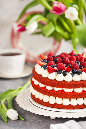 Delicious homemade red velvet cake decorated with cream and fresh berries 스톡 콘텐츠